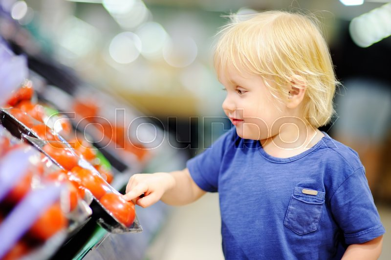Stock image of 'Cute toddler boy in a food store or a supermarket choosing fresh tomatoes. Healthy lifestyle for young family with kids'
