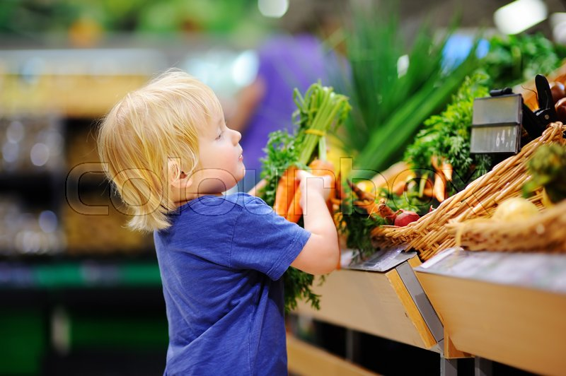 Stock image of 'Cute toddler boy in a food store or a supermarket choosing fresh organic carrots. Healthy lifestyle for young family with kids'