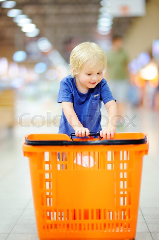 Stock image of 'Toddler boy with shopping cart in a food store or a supermarket. Family shopping'