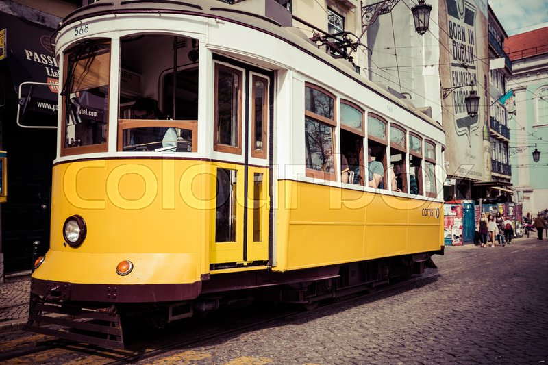 Editorial image of 'Lisboa,Portugal-April 12,2015: A traditional tram is making its way through a narrow street in Lisbon, Portugal on June 3, 2013. The five urban tramway lines mainly serve as a tourist attraction.'