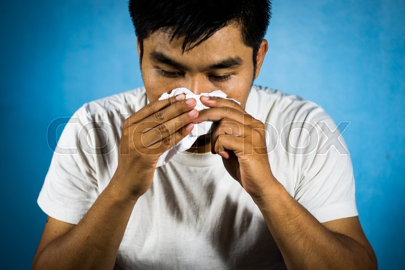 Stock image of 'Asian Man have Cold, flu or allergy symptoms and use toilet paper to wipe snot.'