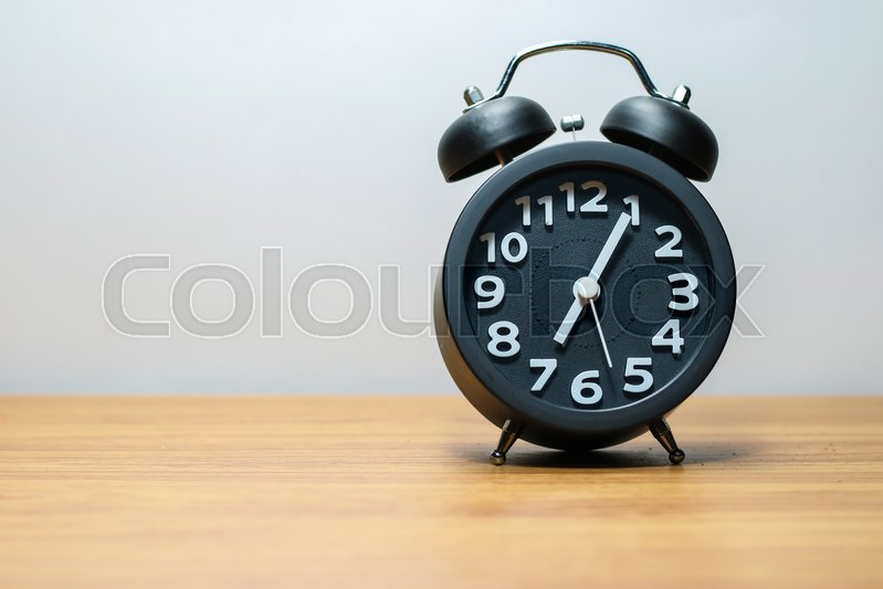 Stock image of 'Black alarm clock place on wood table in burred background'