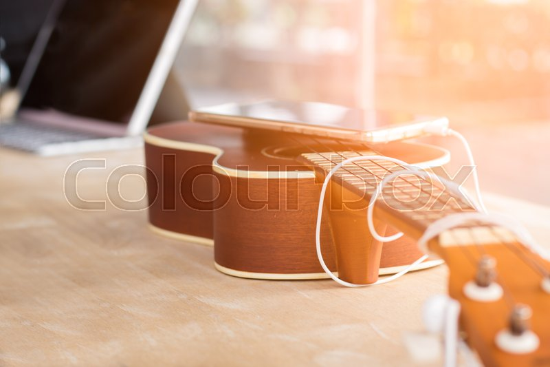 Stock image of 'Ukulele and smartphones. Placed on a wooden table In coffee shop. The background blur of a notebook and the morning light / vintage tone.'