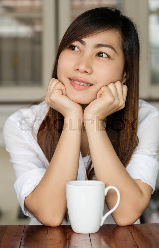Stock image of 'Asian woman smiling happily with drinking coffee in the morning.\'