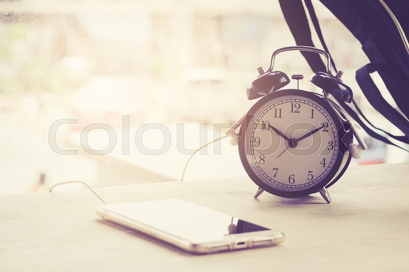 Stock image of 'Alarm clock, coffee smartphone is placed on a wooden table in a coffee shop.'