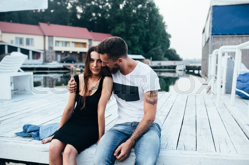 Stock image of 'beautiful couple posing on a wooden pier at lake'