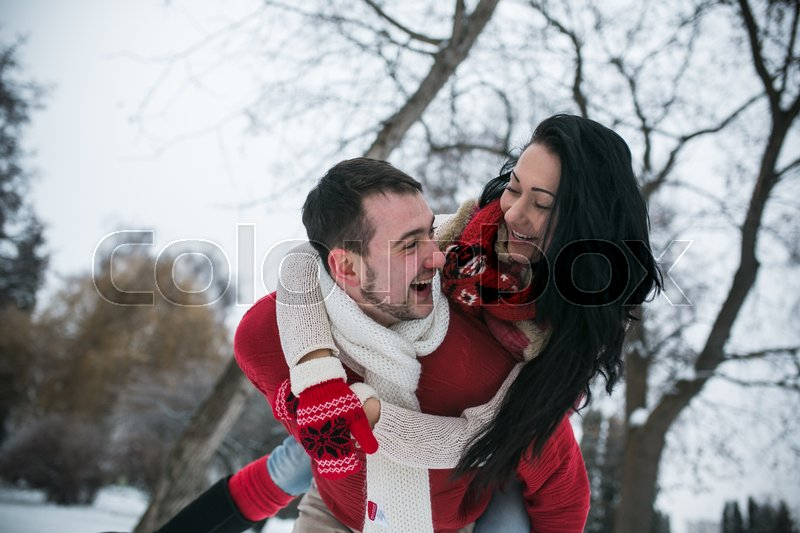 Stock image of 'Man and woman having fun in the snow-covered park'