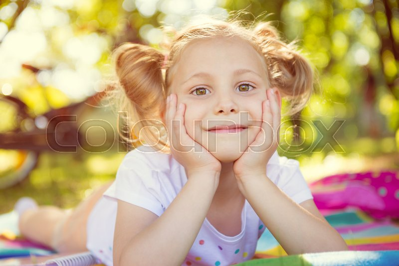 Excited face of pretty small girl in summer park, stock photo