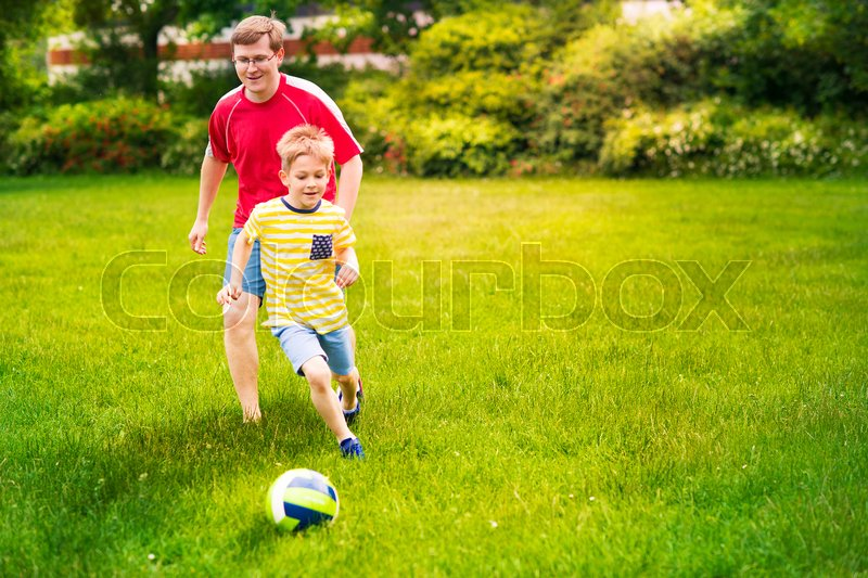 Stock image of 'Sports happy family plays football in sunny summer park'