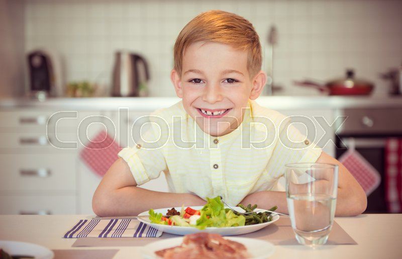 Stock image of 'Young diligent happy boy  at a table eating healthy meal using cutlery'