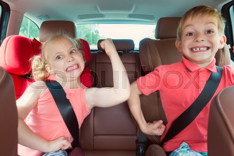 Stock image of 'Happy kids, adorable girl with her brother sitting together in modern car locked with safety belts enjoying family vacation trip on summer weekend'