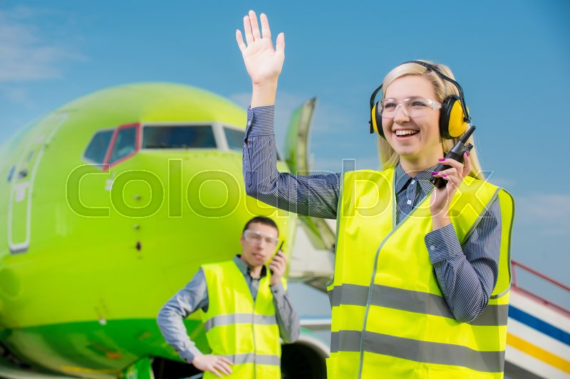 Stock image of 'Airport workers with airplane on the background'