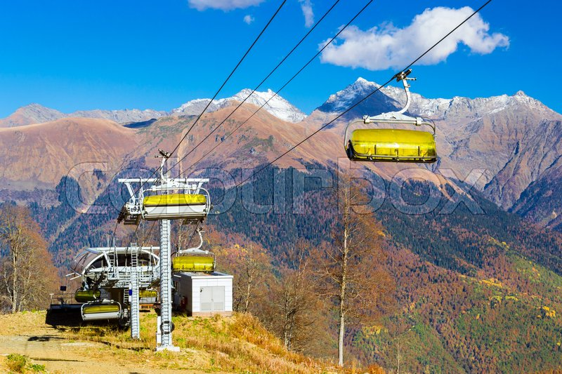 Stock image of 'Mountain zipline through autumn forest on backdrop of Caucasus mountains, funicular railway to observation deck tops 2320 m. Krasnaya Polyana - Alpine ski resort, constructed from 2003 to 2011 for Sochi Olympic games. Rosa Khutor, Sochi, Russia'