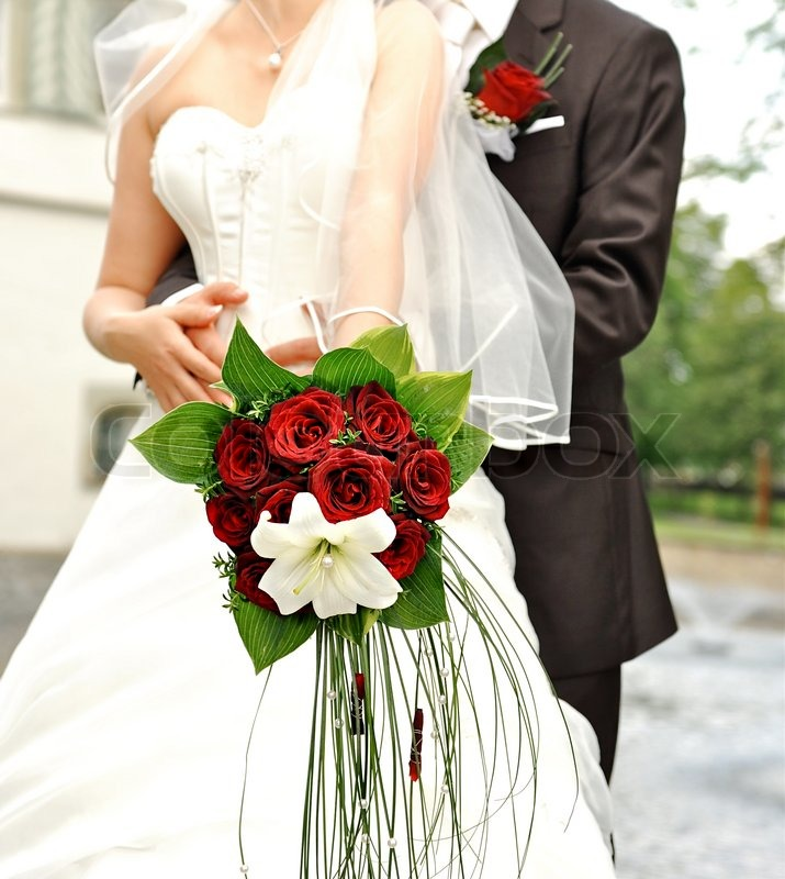 bride holding beautiful red roses wedding flowers bouquet