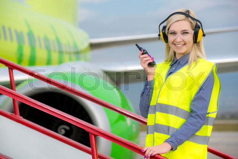Stock image of 'Aircraft engineer with CB radio standing in front of a commercial airliner'