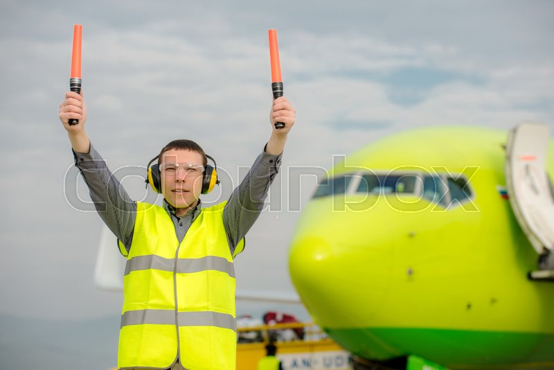 Stock image of 'air traffic controller holding light signs at the airport'