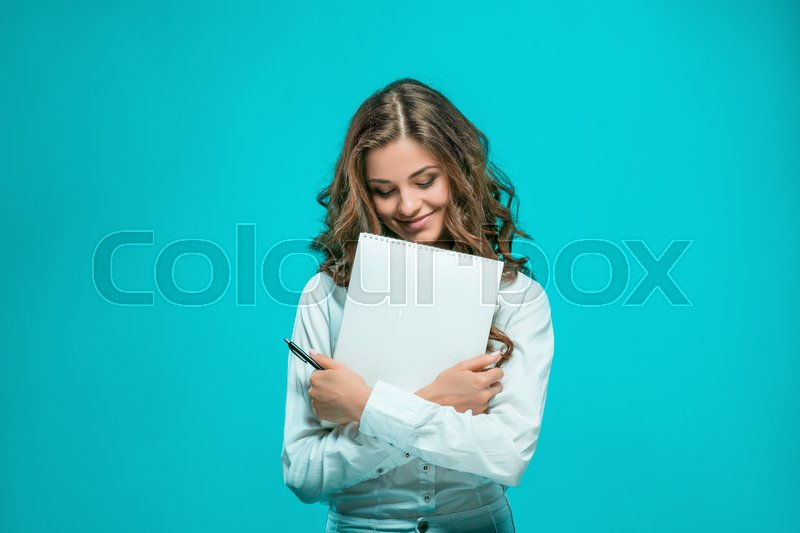 Stock image of 'The smiling young business woman with pen and tablet for notes on blue background'