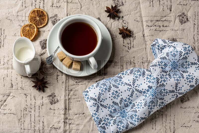 Stock image of 'Cup of hot tea and small milk jug on decorative tablecloth'
