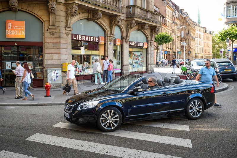 Editorial image of 'STRASBOURG, FRANCE - APR 7, 2016: Man driving beautiful Volvo C70 Convertible car crossing pedestrian walk in the center of the French city of Strasbourg, Alsace on a summer day with pedestrians and tourists'