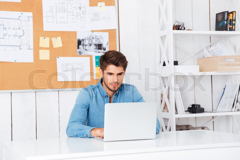 Stock image of 'Pensive handsome bearded casual businessman sitting with laptop at office'