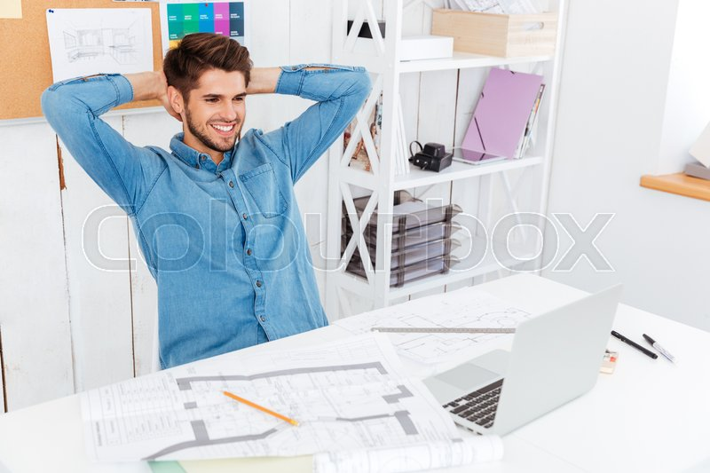 Stock image of 'Businessman stretching hands at his workplace in office and looking at laptop'