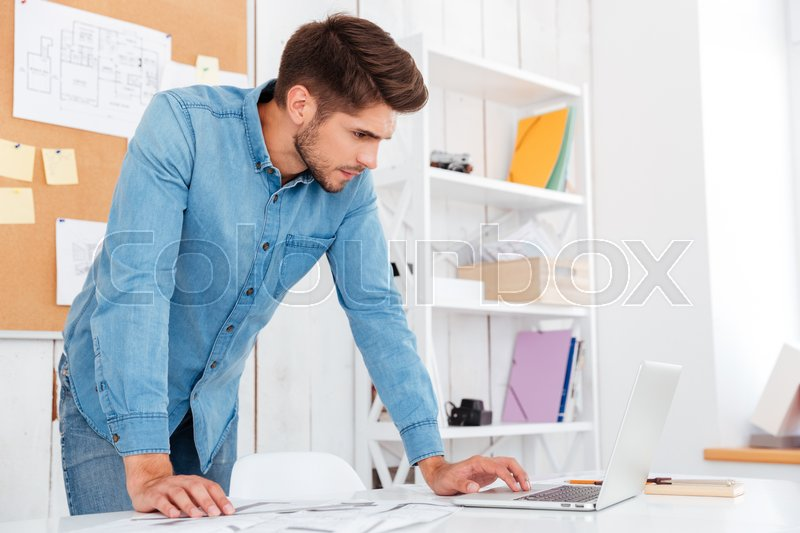 Stock image of 'Pensive young handsome businessman using laptop while standing in office'