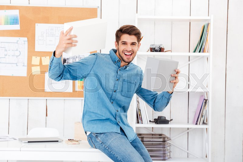 Stock image of 'Cheerful young casual man holding boxes while sitting at the desk in office'