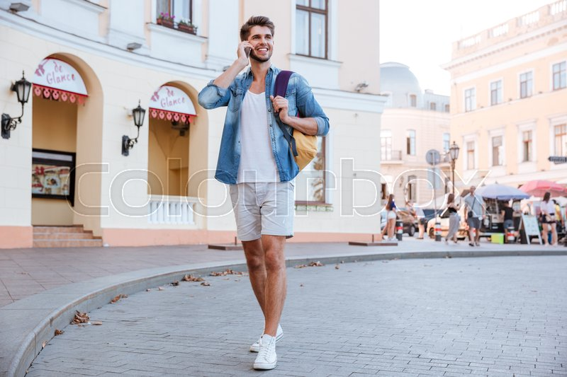 Stock image of 'Full length of happy young man walking and talking on cell phone on the street'