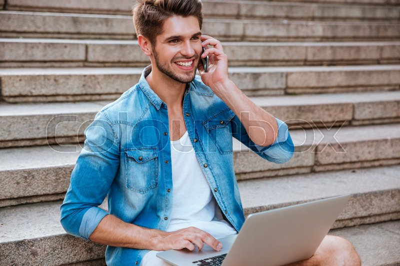 Stock image of 'Smiling cheerful man with laptop talking on mobile phone while sitting on the staircase outdoors'