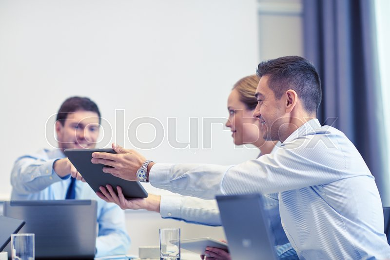 Stock image of 'business, people and technology concept - smiling business team with tablet pc computer meeting in office'