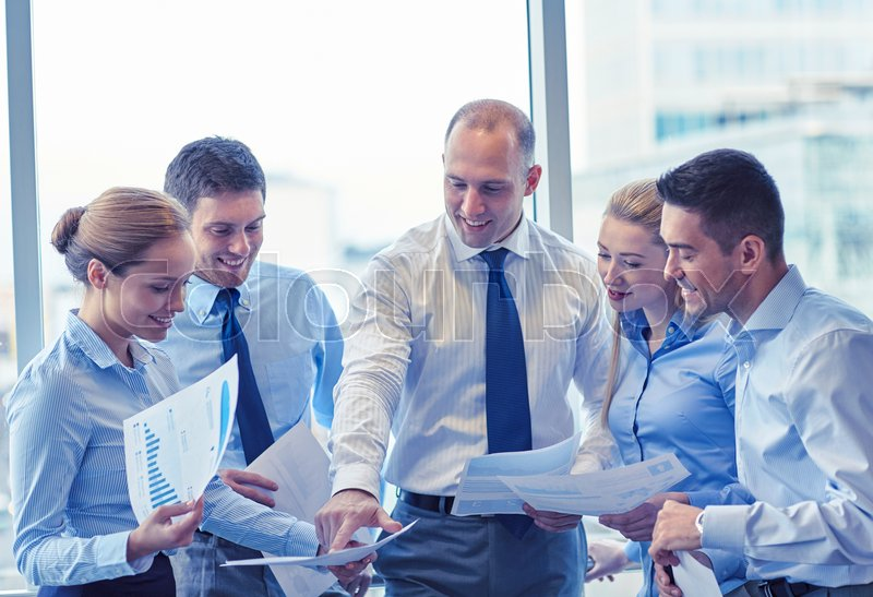 Stock image of 'business, teamwork, people and technology concept - smiling business team with papers meeting and talking in office'
