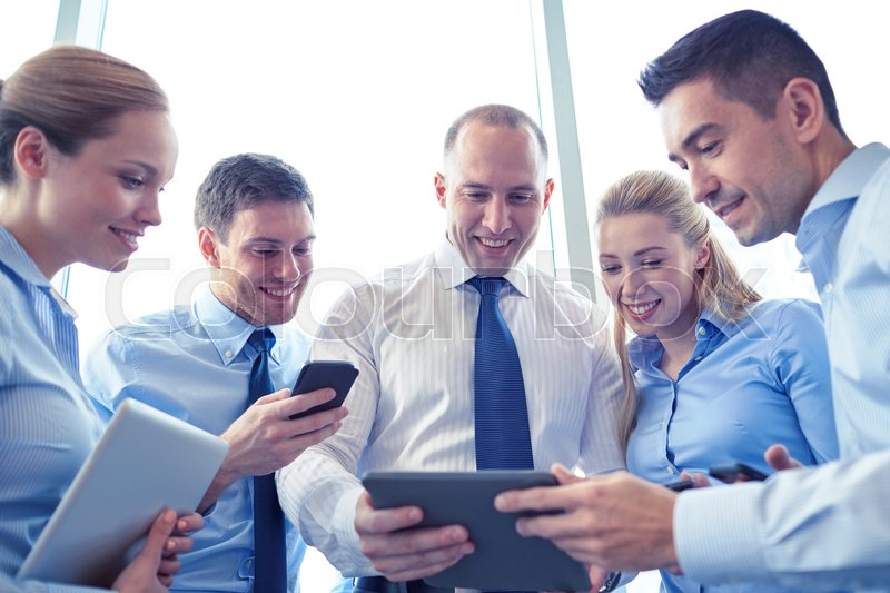 Stock image of 'business, teamwork, people and technology concept - business team with tablet pc and smartphones meeting in office'