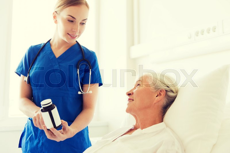 Stock image of 'medicine, age, health care and people concept - doctor or nurse showing medicine to senior woman at hospital ward'