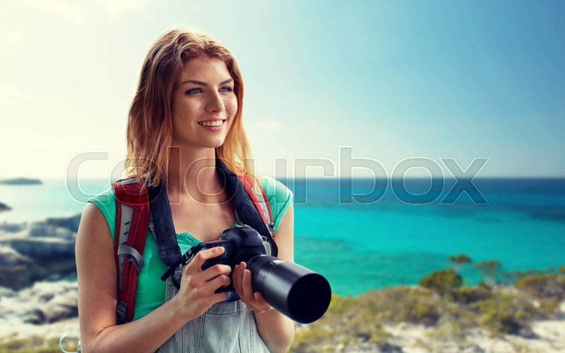 Stock image of 'adventure, travel, tourism, hike and people concept - happy young woman with backpack and camera photographing over seashore or beach background'