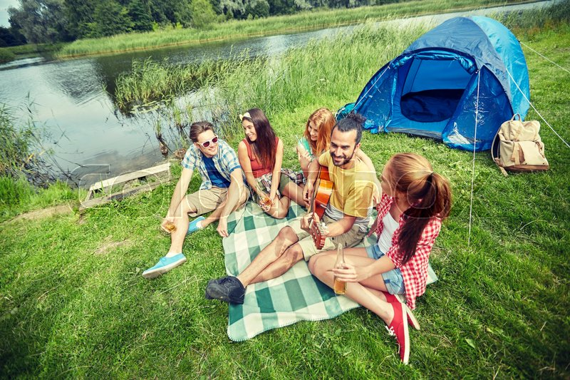 Stock image of 'travel, tourism, hike, picnic and people concept - group of happy friends with tent and drinks playing guitar at camping'