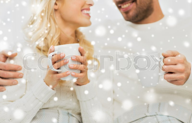 Stock image of 'winter, love, family and happiness concept - close up of happy couple with tea cups at home'
