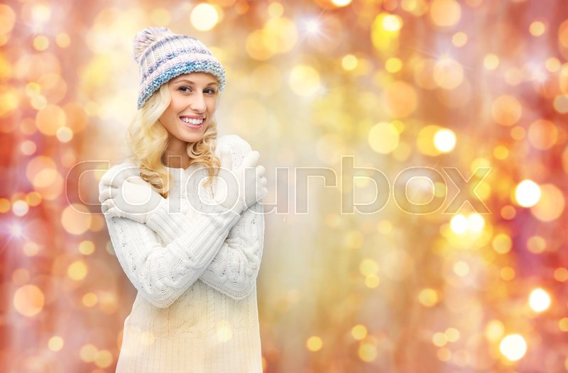 Stock image of 'winter, holidays, christmas and people concept - smiling young woman in winter hat, sweater and gloves over lights background'