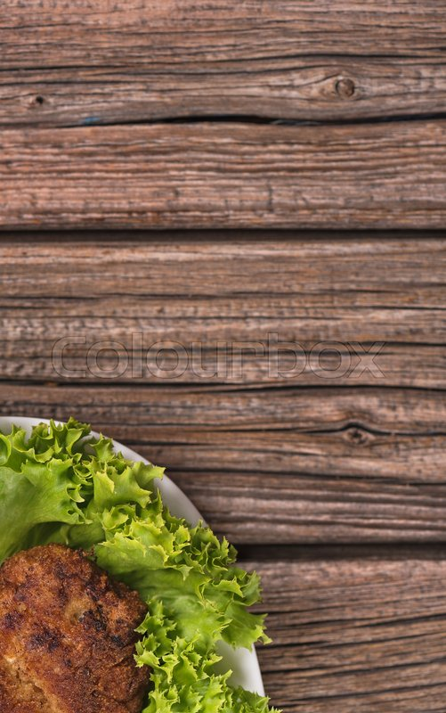 Stock image of 'Delicious baked cutlet over wooden surface with copy space for your text'