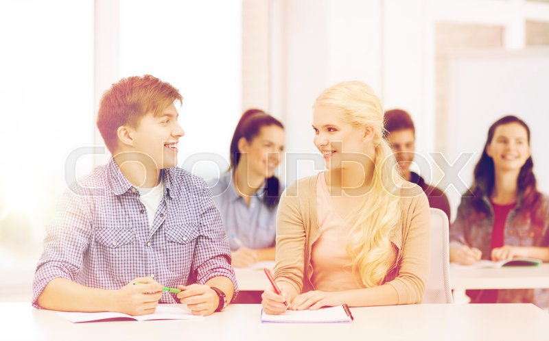 Stock image of 'education, school and people concept - two teenagers with notebooks looking at each other at school'