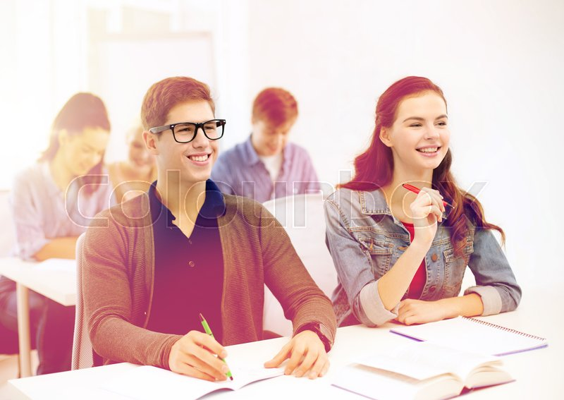 Stock image of 'school and education concept - group of smiling students with notebooks at school'