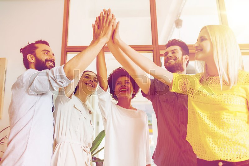 Stock image of 'business, startup, gesture, people and teamwork concept - happy creative team making high five in office'