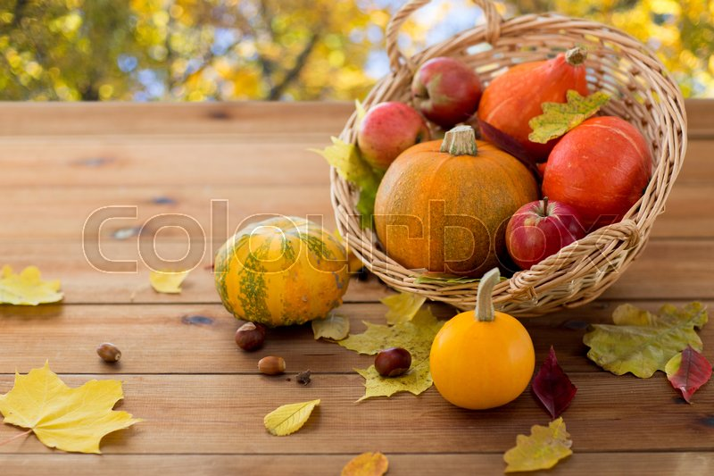 Stock image of 'harvest, season and autumn concept - close up of pumpkins in wicker basket with leaves on wooden table over natural background'