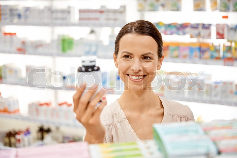 Stock image of 'medicine, pharmaceutics, health care and people concept - happy female customer with drug jar at pharmacy'