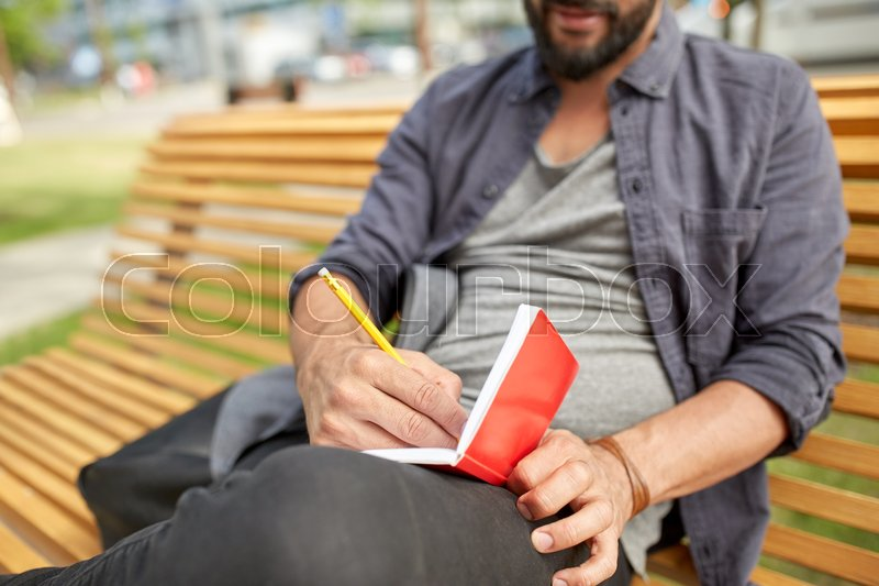 Stock image of 'lifestyle, freelance, inspiration and people concept - close up of man with bag writing to notebook or diary sitting on city street bench'