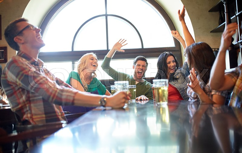 Stock image of 'people, leisure, friendship and entertainment concept - happy friends drinking beer, watching sport game or football match and celebrating victory at bar or pub'