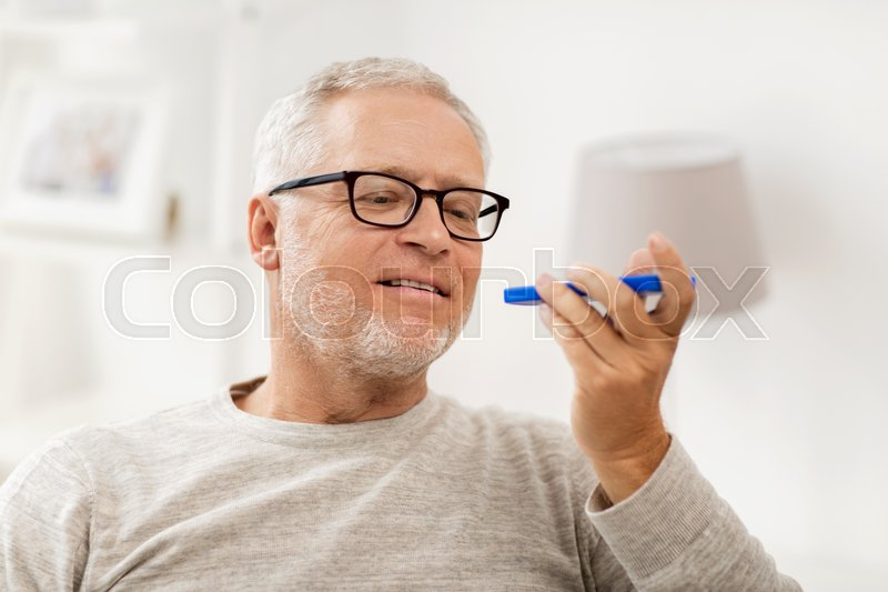 Stock image of 'technology, people, lifestyle and communication concept - happy senior man using voice command recorder or calling on smartphone at home'