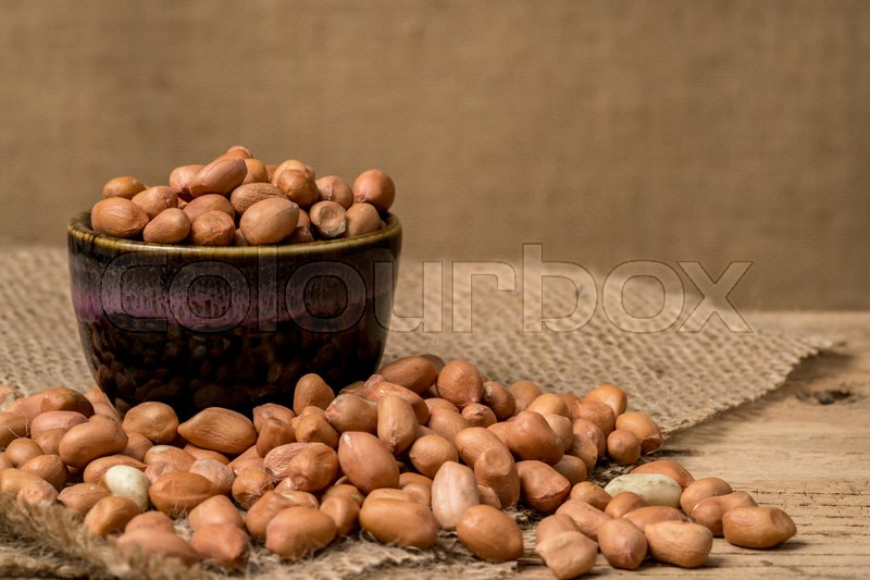Stock image of 'Peanuts in ceramic bowl on brown sack'