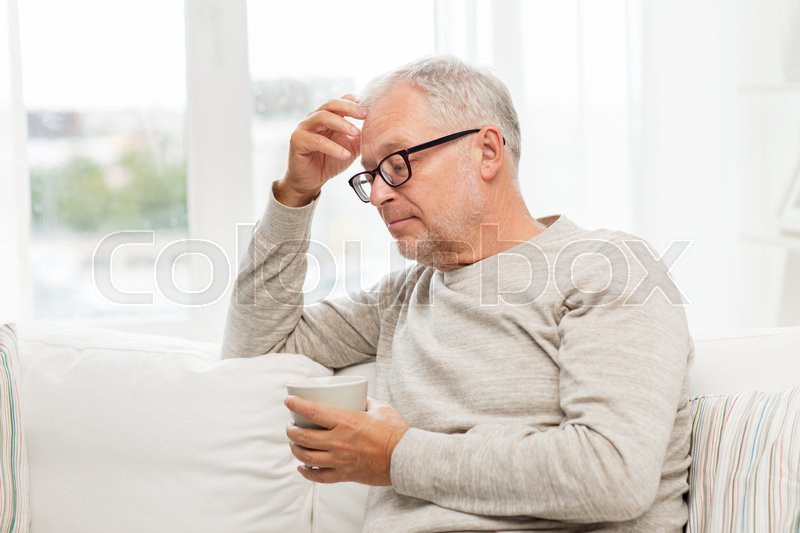 Stock image of 'old age, drink and people concept - senior man with cup of tea at home'