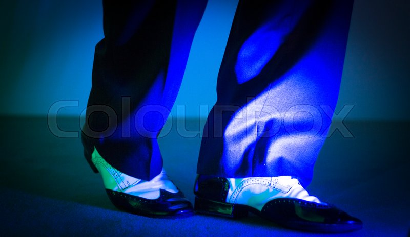 Stock image of 'Male latin and salsa dancer in black and white jazz dancing shoes in light and dark blue lights on stage.'