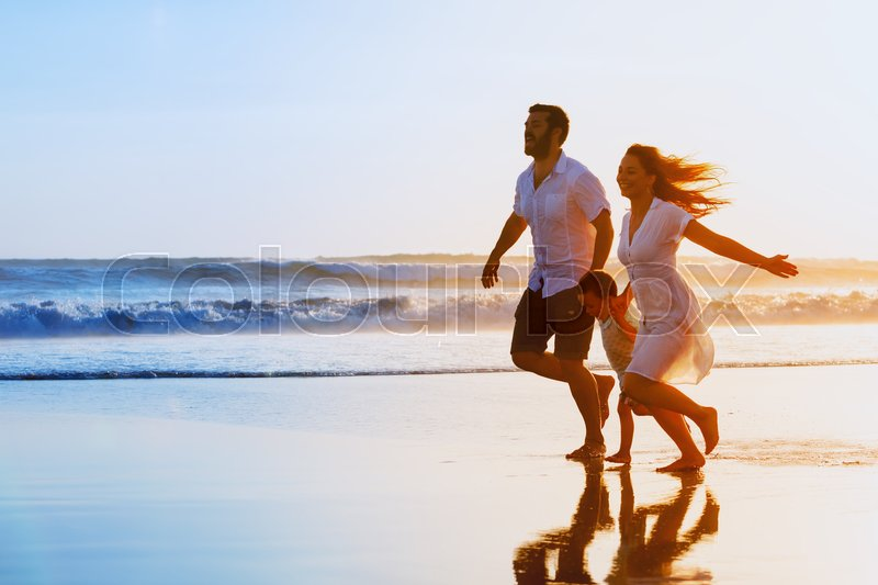 Stock image of 'Happy family - father, mother, baby son hold hands and run together with fun along sunset sea surf on black sand beach. Travel, active lifestyle, parents with children on tropical summer vacations.'
